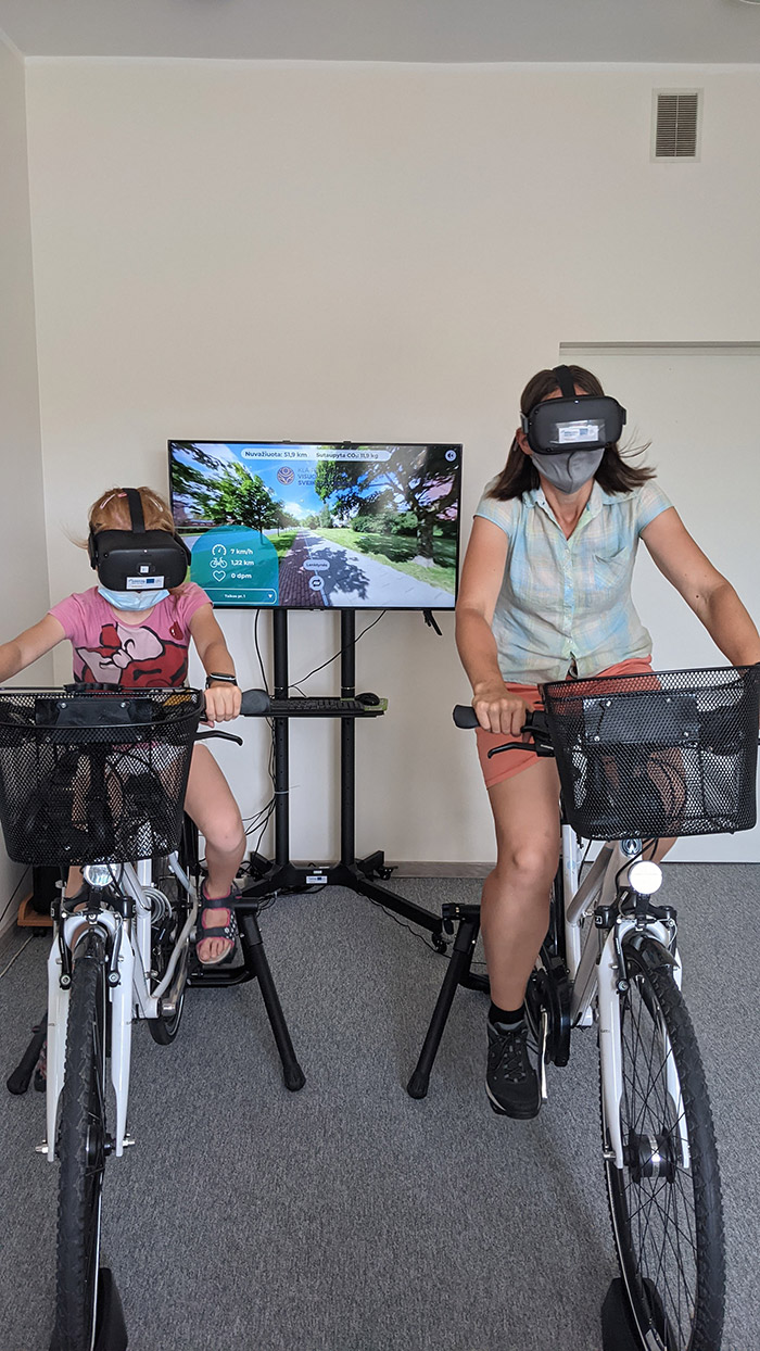 A child and an adult riding indoor bicycles wearing virtual reality glasses.