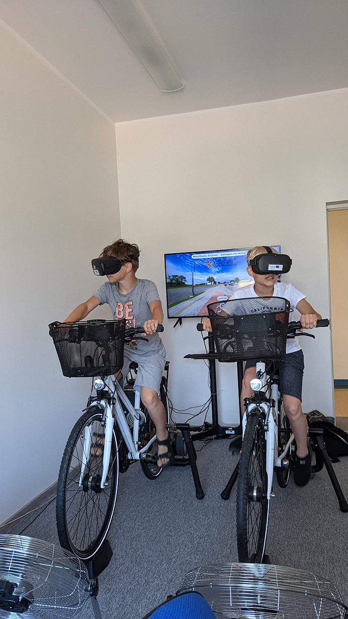 Two children riding indoor bicycles wearing virtual reality glasses.