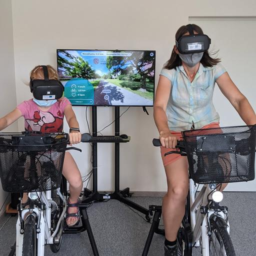 Two persons rinding indoor bicycles wearing virtual reality glasses.