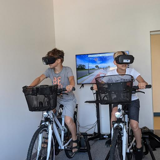 Two persons riding indoor bicycles wearing virtual reality glasses.
